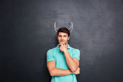 Pensive young man with drawn horns standing and pretending devil Stock Image