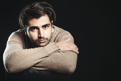 Pensive young man with folded arms. Looking at the camera. Trendy hair, brown sweater and dark background stock images