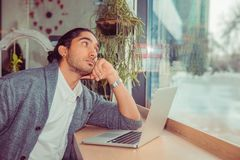 Pensive young man in front of the laptop looking to side thoughtful royalty free stock images