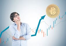 Pensive young man in glasses, bitcoin, graphs Royalty Free Stock Photography