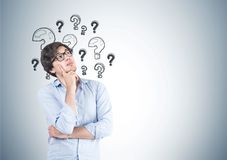 Pensive young man in glasses, questions Royalty Free Stock Image