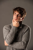 Pensive young man in gray pullover Stock Photo