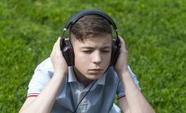 Young man with headphones listening to music. Pensive Young man with headphones listening to music Royalty Free Stock Image