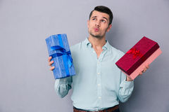 Pensive young man holding two gift box Royalty Free Stock Photography