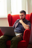 Pensive young man with laptop Royalty Free Stock Photography