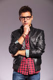 Pensive young man with leather jacket and glasses Stock Images