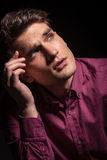 Pensive young man looking up. While holding his hand to the forehead Royalty Free Stock Photos