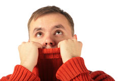 Pensive young man looks upward hiding in sweater Royalty Free Stock Photos