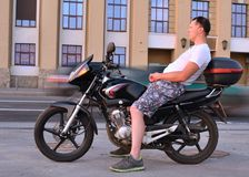Pensive young man with motorcycle Royalty Free Stock Photo