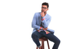 Pensive young man sitting on a chair. Royalty Free Stock Images