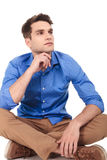 Pensive young man sitting with his legs crossed. Looking away from the camera, thinking Stock Photos