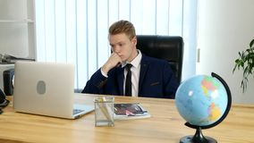 A pensive young man sitting in his office at work stock video