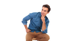 Pensive young man sitting and laughing to side. Isolated on white background Royalty Free Stock Images