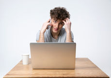 Pensive young man sitting at the table with laptop Royalty Free Stock Image