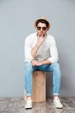Pensive young man in sunglasses sitting and thinking Stock Photo