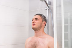 Pensive young man taking a shower in the bathroom. Pensive young man taking a shower and thinking about something while standing under flowing water in shower Royalty Free Stock Photos
