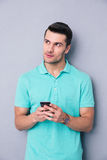 Pensive young man using smartphone Royalty Free Stock Images