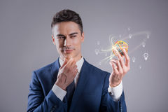 Pensive young man is watching at sphere. What ideas should I choose. Portrait of elegant pleasant businessman is expressing thoughtfulness while looking at Stock Photo