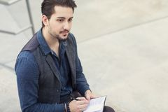 A pensive young man writing in his pocket size notebook. Looking afar Royalty Free Stock Photos