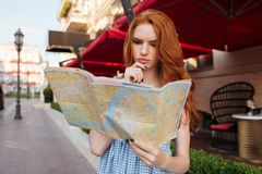 Pensive young redhead girl looking at a guide map Royalty Free Stock Image