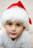 Pensive Young Santa. Portrait of the young boy in a cap of Santa Claus Royalty Free Stock Images