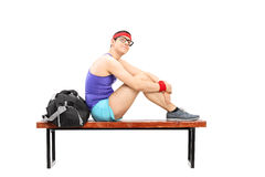 Pensive young sportsman sitting on a bench Stock Photography