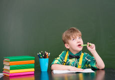 Pensive young student near empty green chalkboard Stock Photo