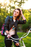Pensive young woman on bicycle in green park on sunset Stock Images