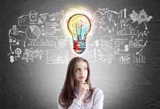 Pensive young woman with business ideas. Pensive young woman with long hair is standing near a blackboard with a colorful light bulb and a business scheme Royalty Free Stock Images
