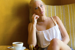 Pensive young woman at cafe with coffee and smartphone Royalty Free Stock Image