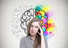 Pensive young woman, creativity vs exact knowledge. Pensive young woman wearing a striped shirt standing with her hand near the forehead and thinking. A concrete Royalty Free Stock Photos