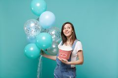 Pensive young woman in denim clothes looking up holding bucket of popcorn celebrating with colorful air balloons