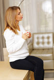 Pensive young woman drinking coffee Stock Photography