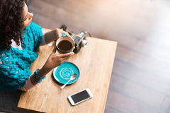 Pensive young woman drinking cup of hot coffee. Top view of dreamful mulatto girl making break in cafe. She is sitting at table and looking aside. Focus on Stock Photo