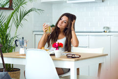 Pensive young woman drinking juice in the kitchen. royalty free stock image
