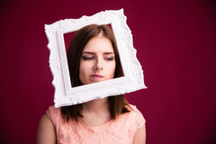 Pensive young woman with frame on head Royalty Free Stock Photography