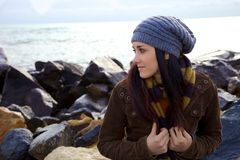 Pensive young woman in front of the ocean in the winter Stock Photos
