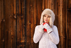 Pensive young woman in furry hat with cup near rustic wood wall Royalty Free Stock Photography
