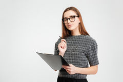 Pensive young woman in glasses holding clipboard and pen Stock Image