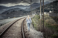 Pensive young woman going away into the distance across railway path in overcast day with dramatic sky  symbolizing parting and de. Pensive young woman running Stock Images
