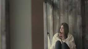 Pensive young woman looking through a window. And drinks hot tea stock video footage