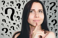 Pensive young woman and lots of question marks stock photo