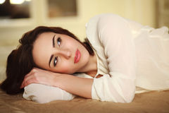Pensive young woman lying on the bed at home Stock Images
