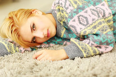Pensive young woman lying on the carpet Stock Photos