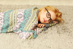Pensive young woman lying on the carpet Stock Photo