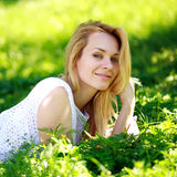 Pensive young woman lying in the green grass, enjoying summer day Royalty Free Stock Images