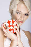 Pensive young woman with a mug of coffee Stock Photos