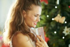Pensive young woman near Christmas tree embracing notebook royalty free stock image