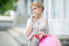 Pensive young woman out of cash after shopping. Portrait of unhappy beautiful person holding open wallet with pensive expression at mall entrance. Young pensive Stock Image
