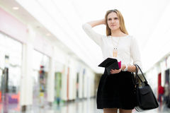 Pensive young woman out of money after shopping time. Confused young woman out of money holding opened wallet in mall, deciding on shopping, economy, tight Stock Photography